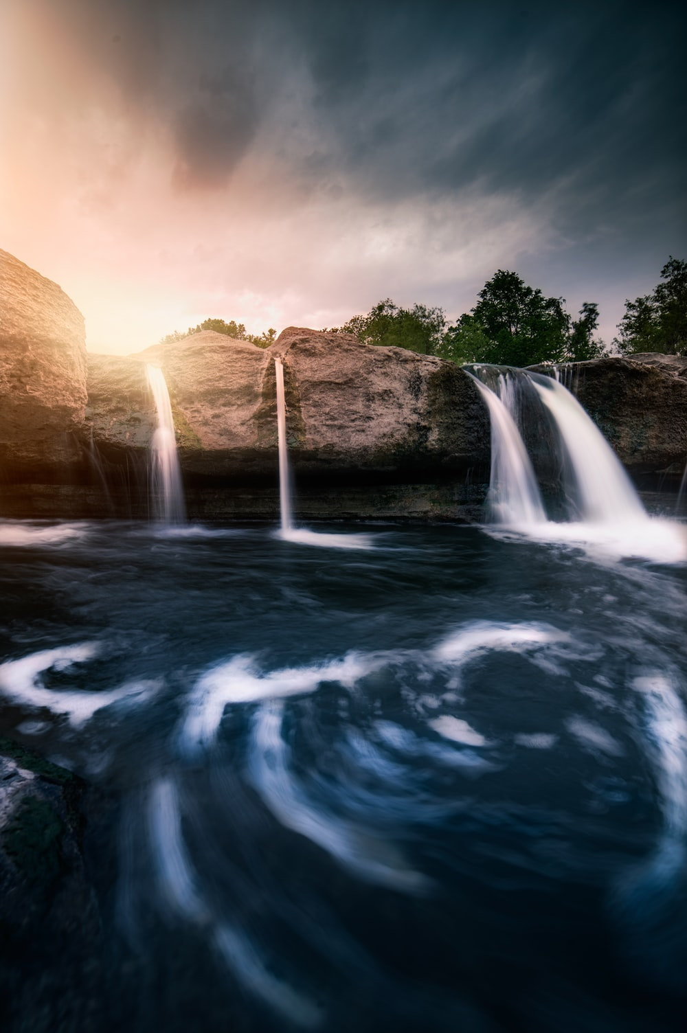 water falls under cloudy sky during daytime