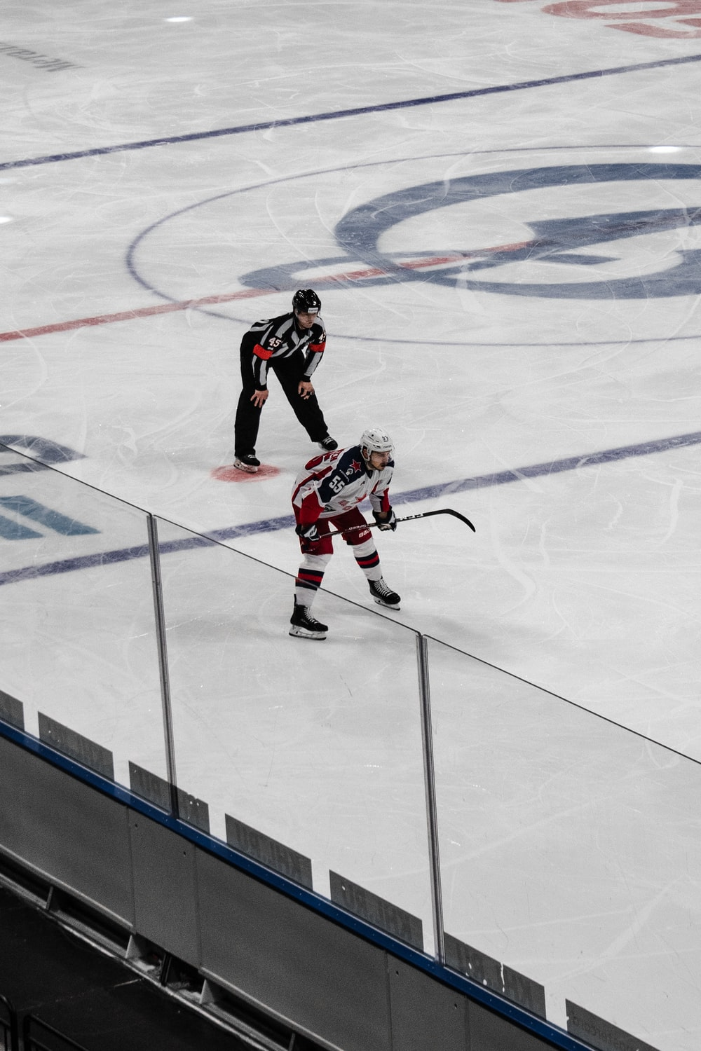 man in black and red ice hockey jersey shirt and black pants playing hockey