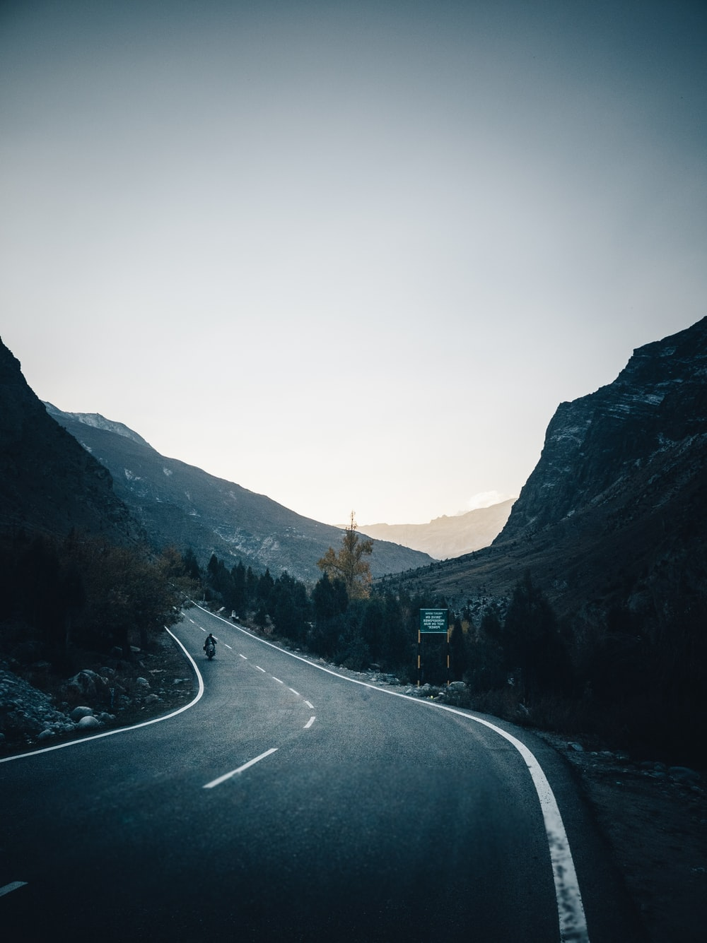 gray asphalt road between mountains during daytime