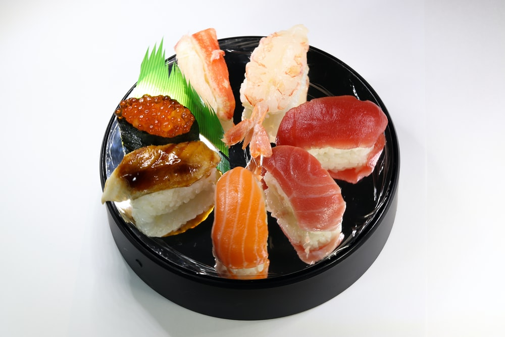 sliced meat with green leaf on black ceramic plate