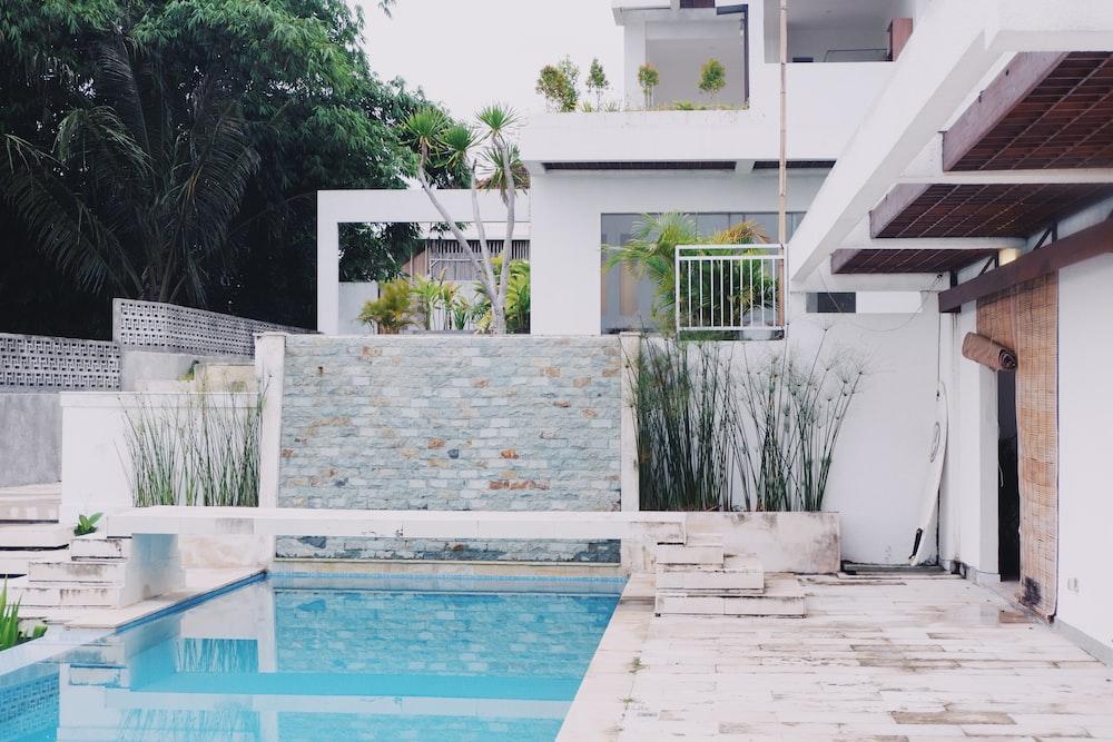 white concrete house near swimming pool during daytime