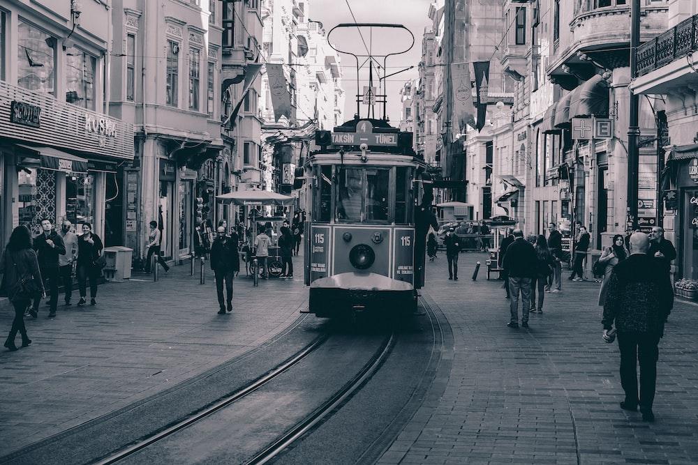 people walking on sidewalk near tram during daytime