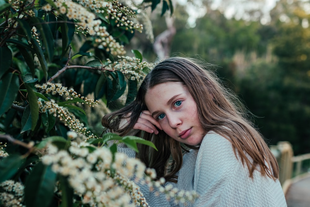 woman in white sweater standing beside green plant during daytime