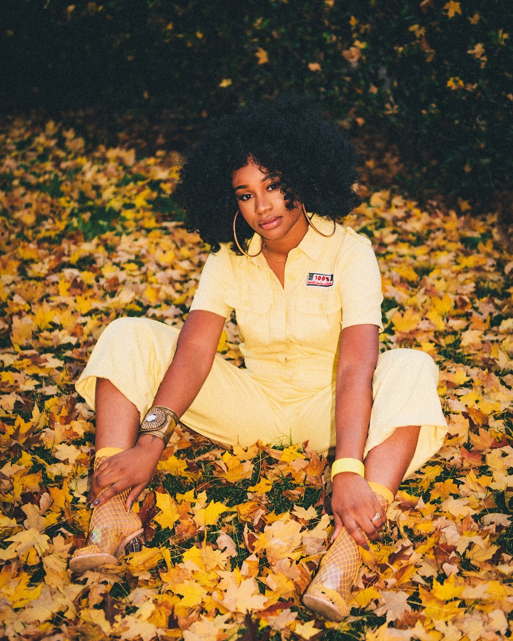 woman in white crew neck t-shirt and yellow shorts sitting on yellow leaves