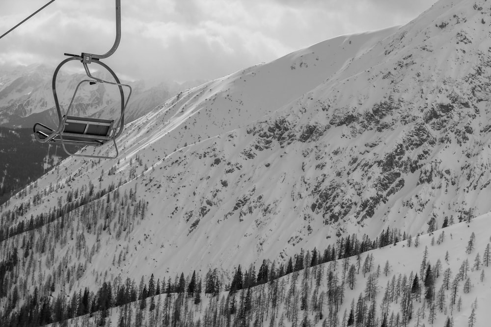 grayscale photo of cable car over snow covered mountain