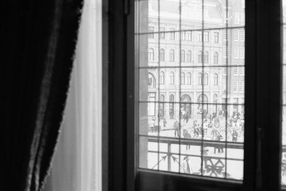 grayscale photo of window with curtain