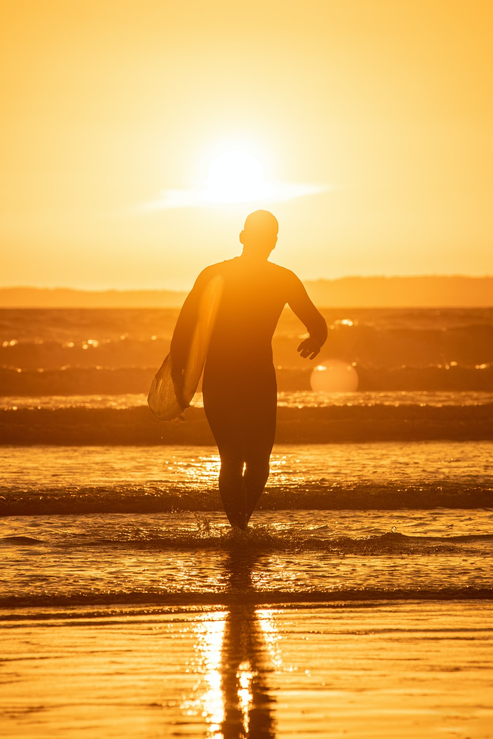 silhouette of man holding surfboard on beach during sunset