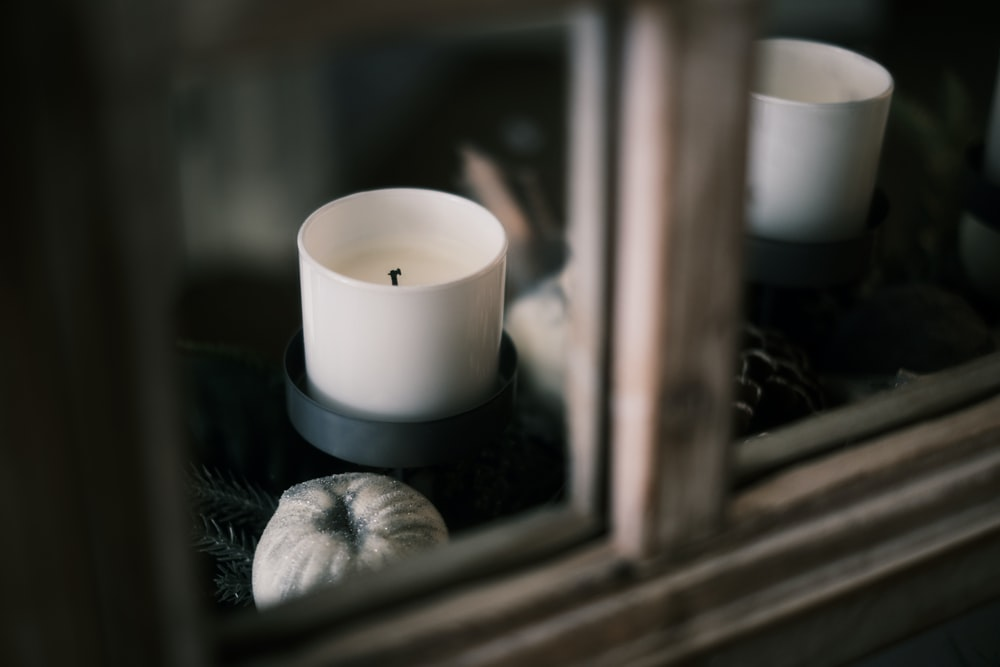 white pillar candle on brown wooden window