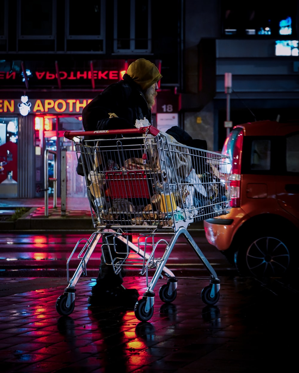 woman in black jacket riding red and silver shopping cart