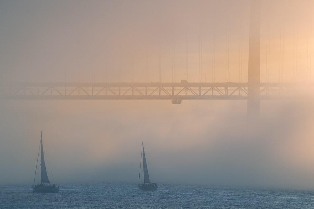 sailboat on sea under bridge during foggy day