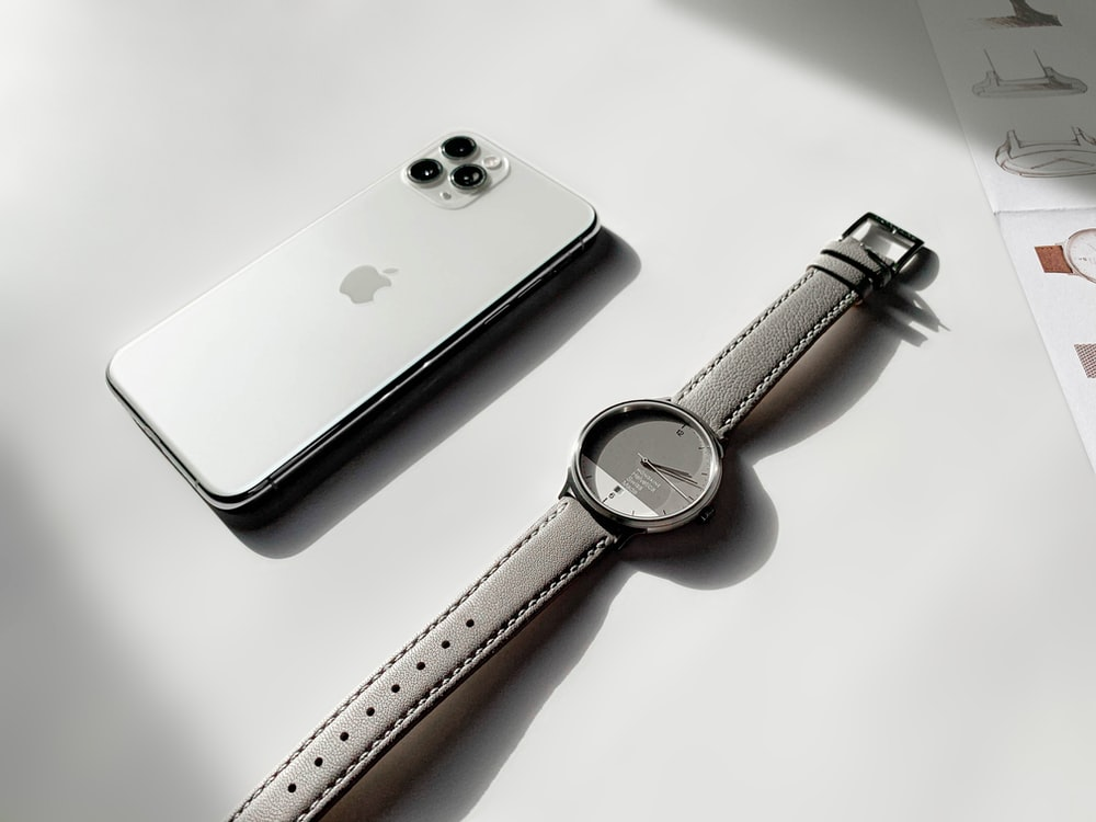 silver iphone 6 beside silver apple watch with brown leather strap