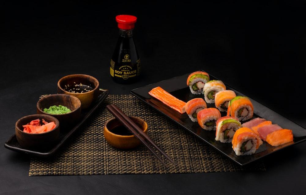 sushi on black ceramic plate beside sauce bottle
