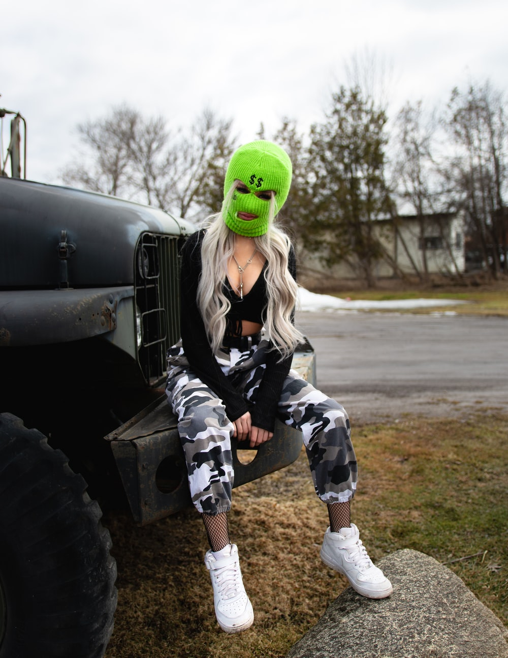 woman in green mask and black jacket sitting on gray metal tank during daytime