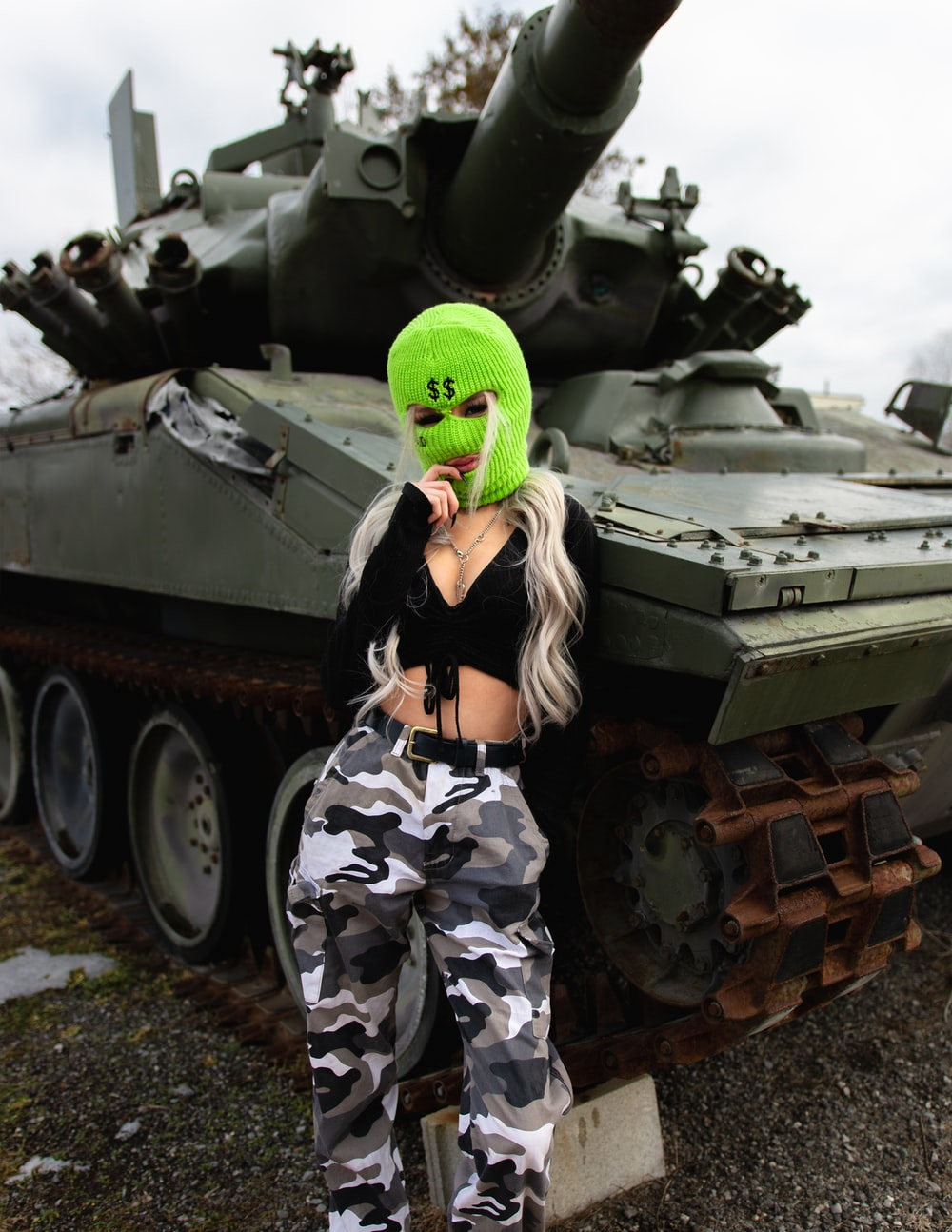 woman in green and black camouflage uniform standing beside green battle tank