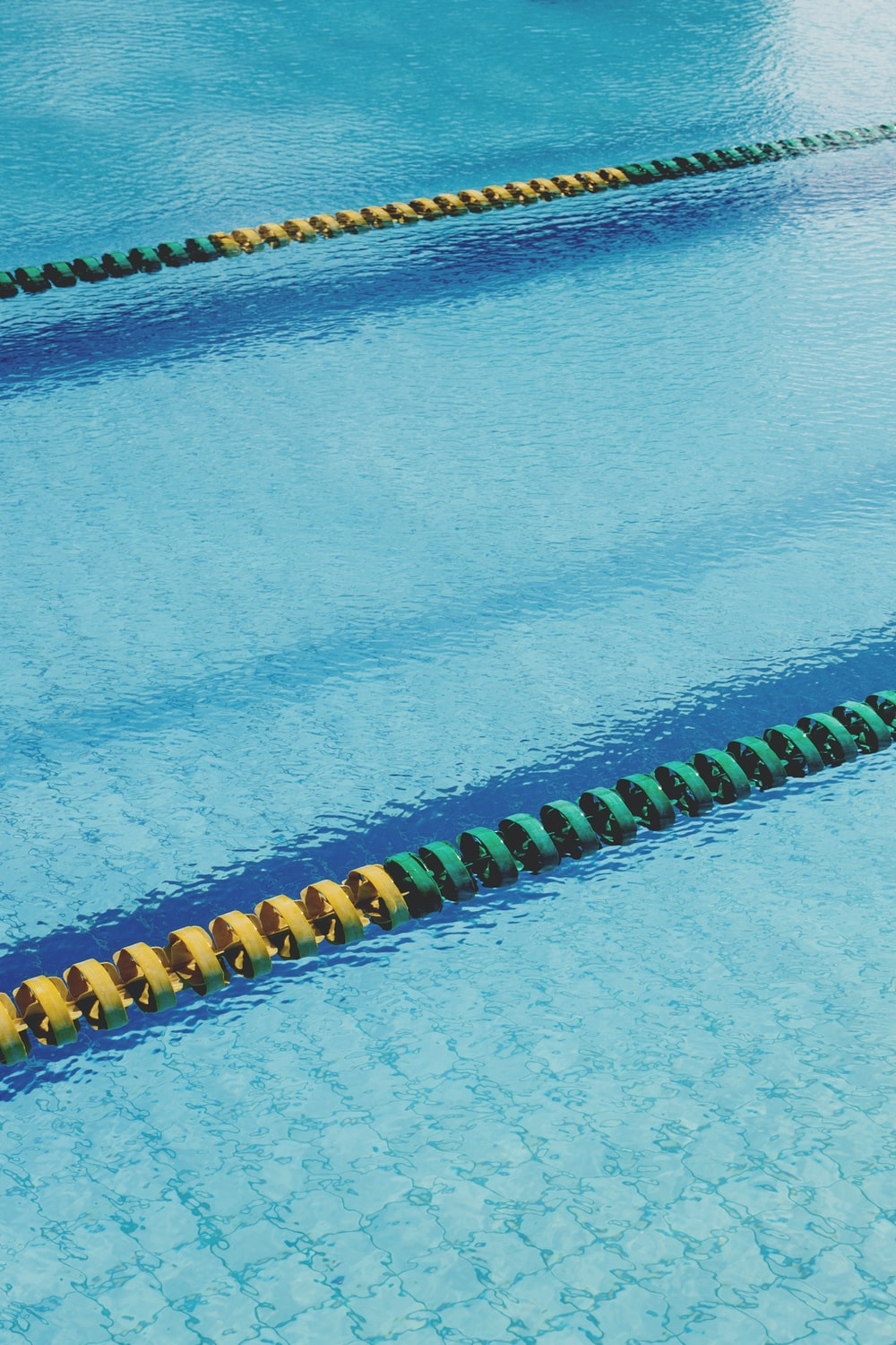 blue swimming pool with yellow and black beaded bracelets