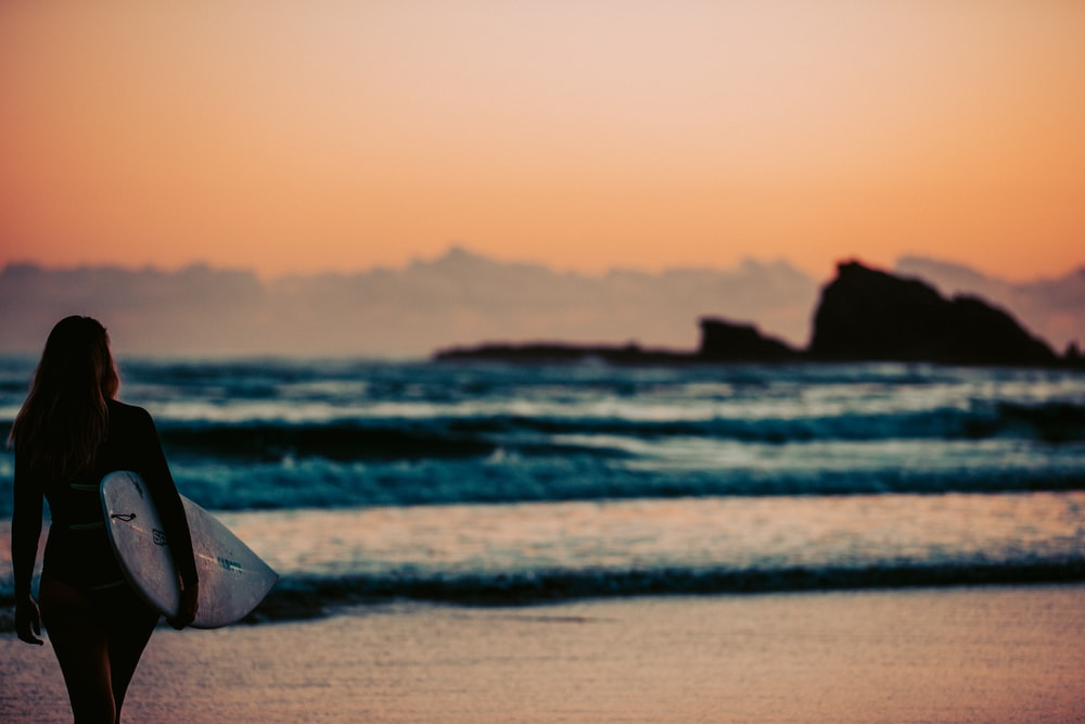 white and brown beach tent on beach during sunset