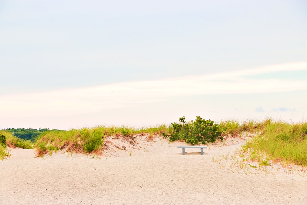 white plastic chair on brown sand during daytime