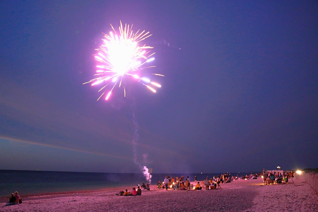people on beach launching fireworks