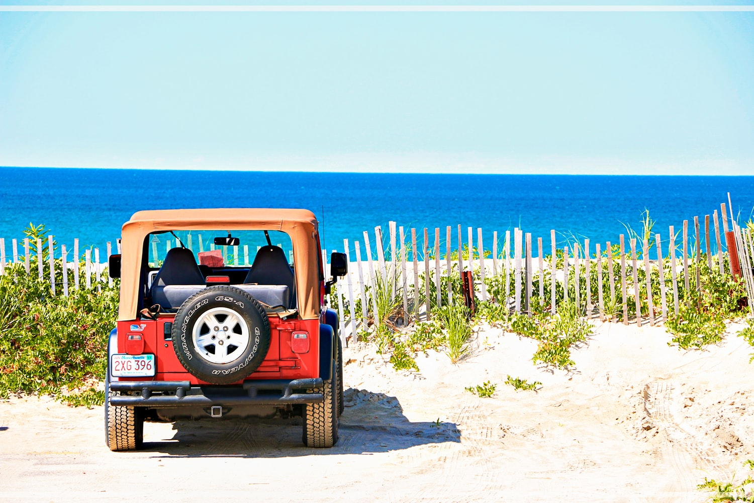 Jeep with Massachusetts plates parked near a beach.