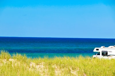 green grass near blue sea under blue sky during daytime cape cod teams background