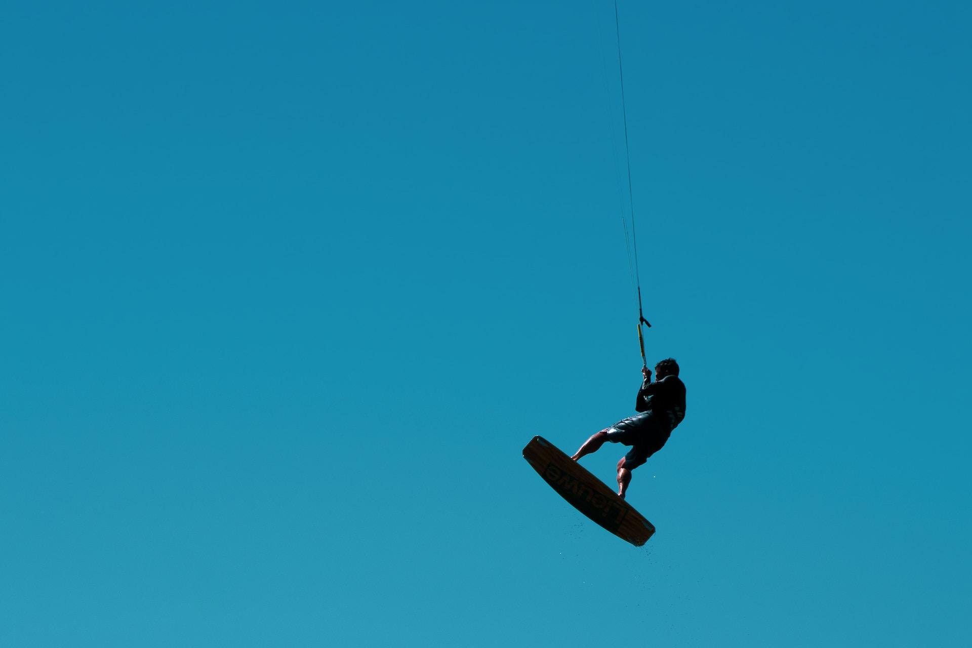 man in black jacket and black pants riding on brown skateboard under blue sky during daytime
