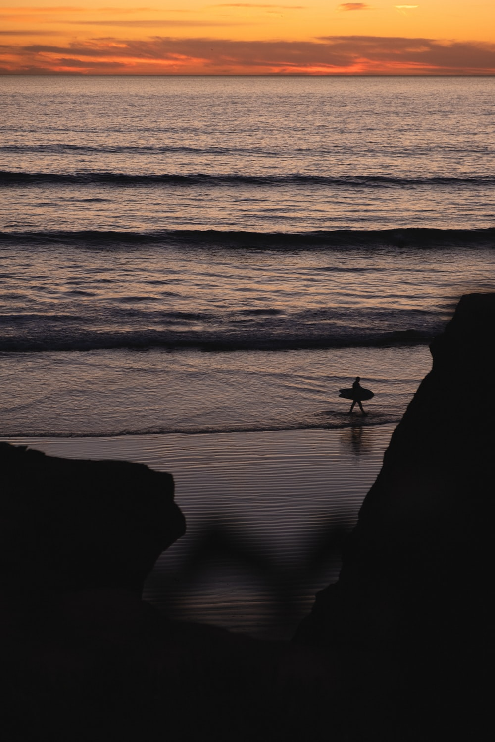 silhouette of 2 people standing on seashore during sunset