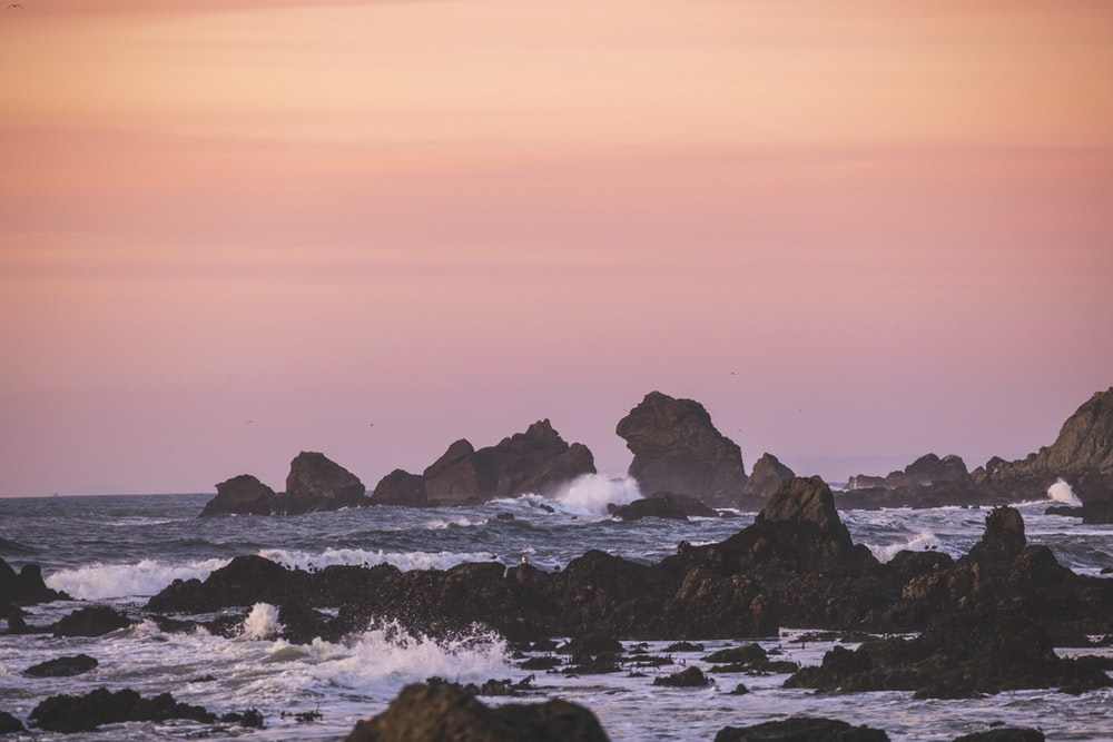 rocky shore with ocean waves during daytime