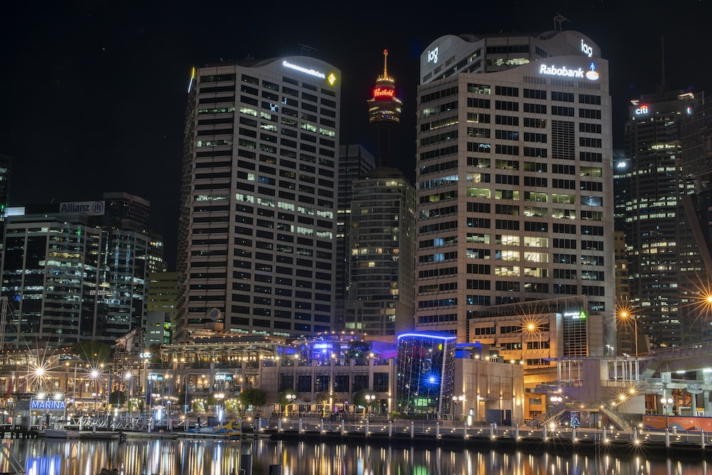 city buildings near body of water during night time