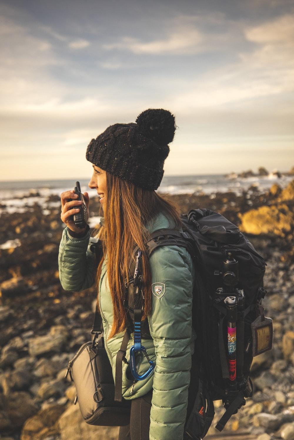 woman in green jacket holding black dslr camera