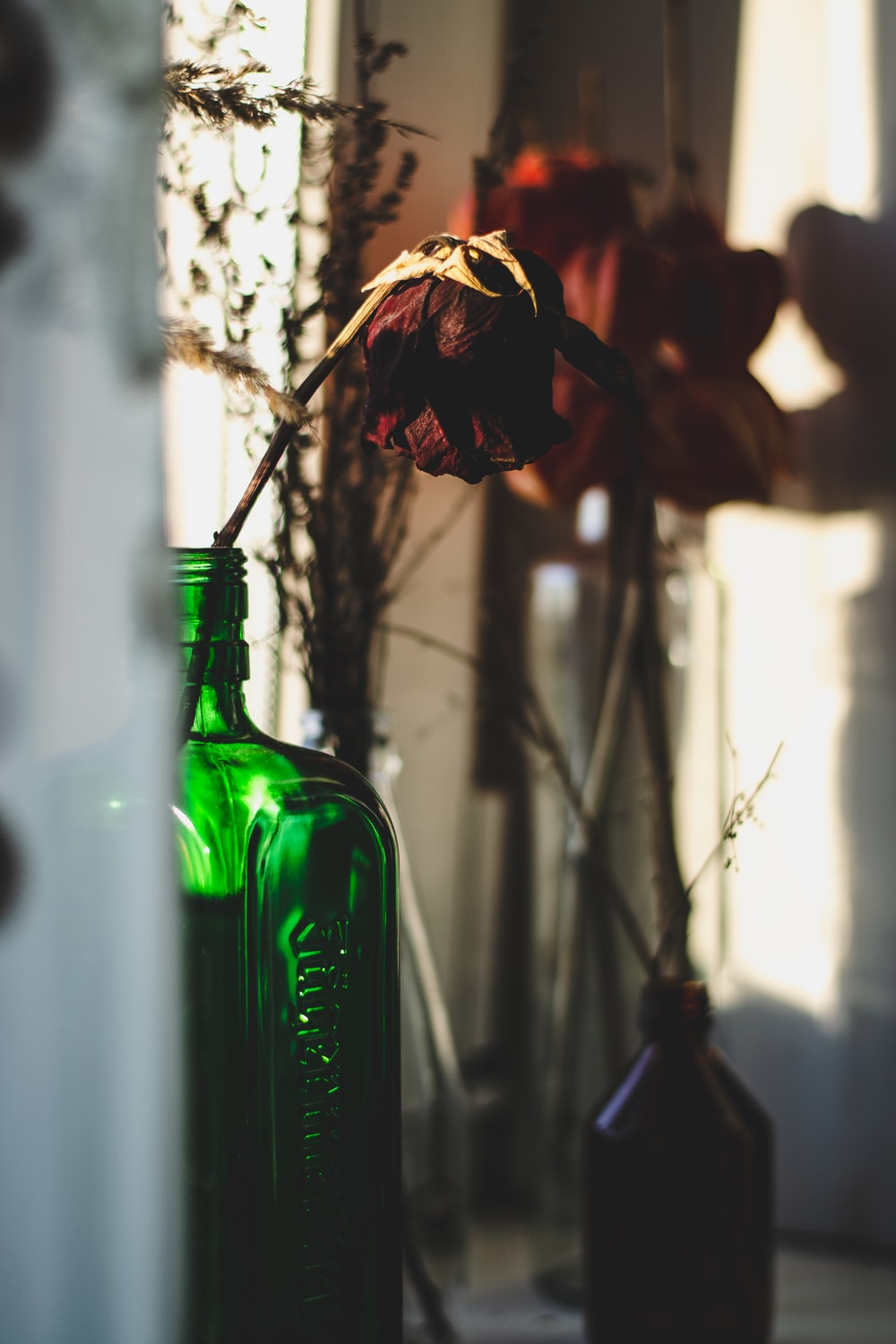 green glass bottle with brown and red flowers