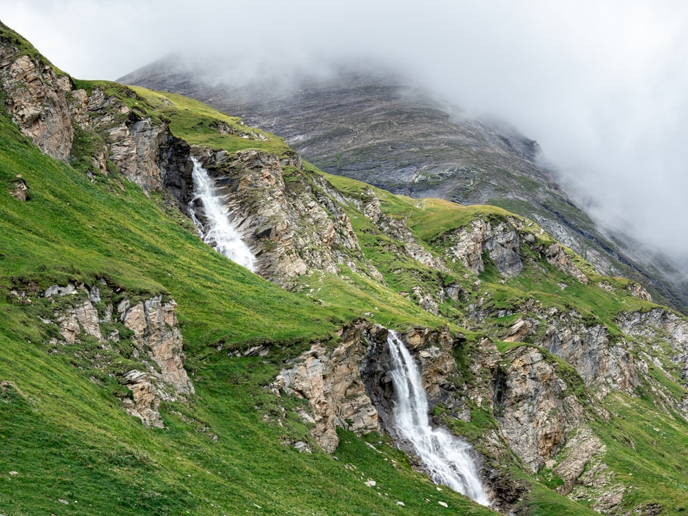 waterfalls on green grass covered mountain