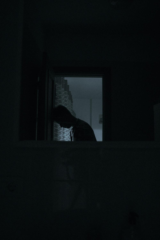 person in black jacket standing near window