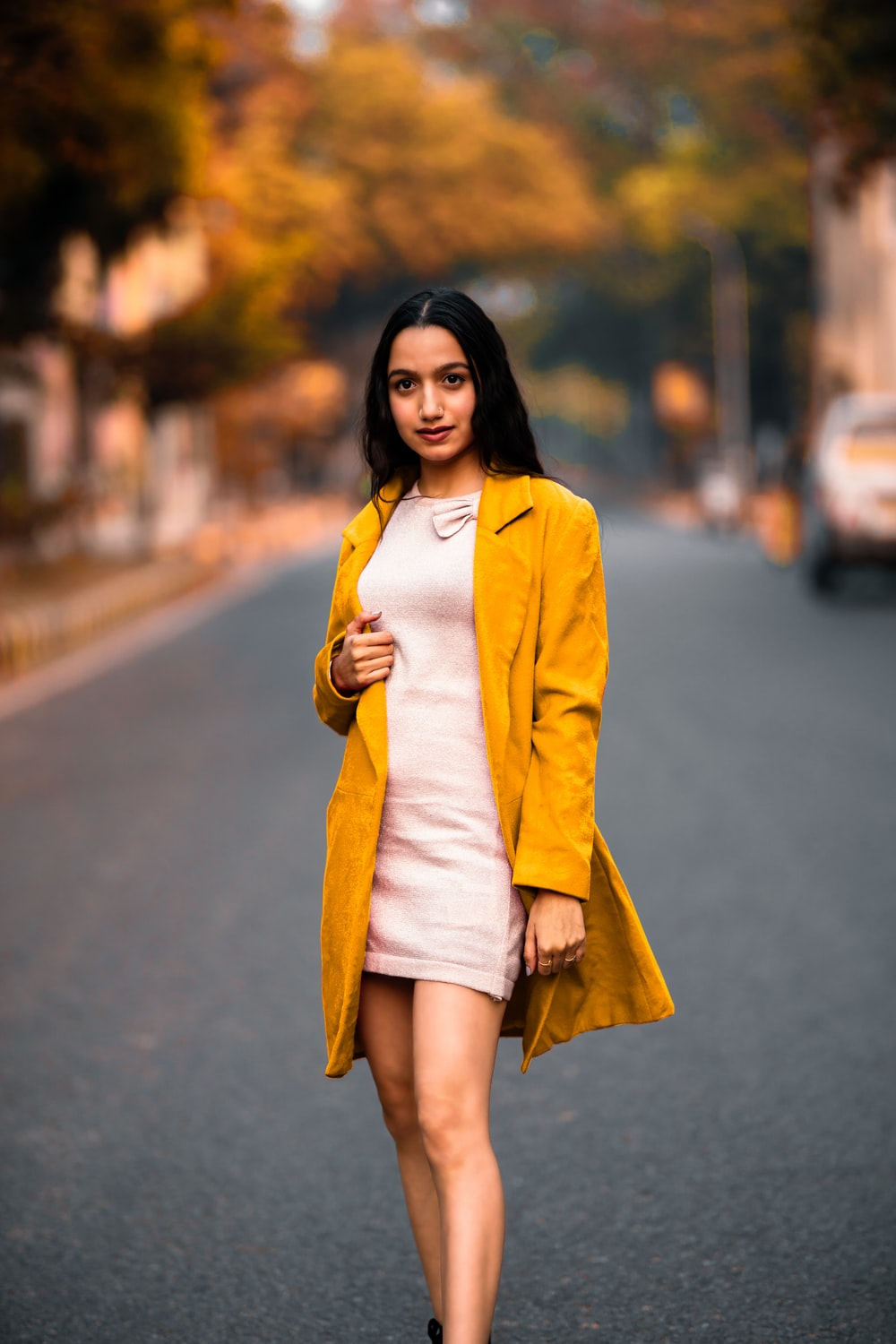 woman in yellow blazer standing on road during daytime