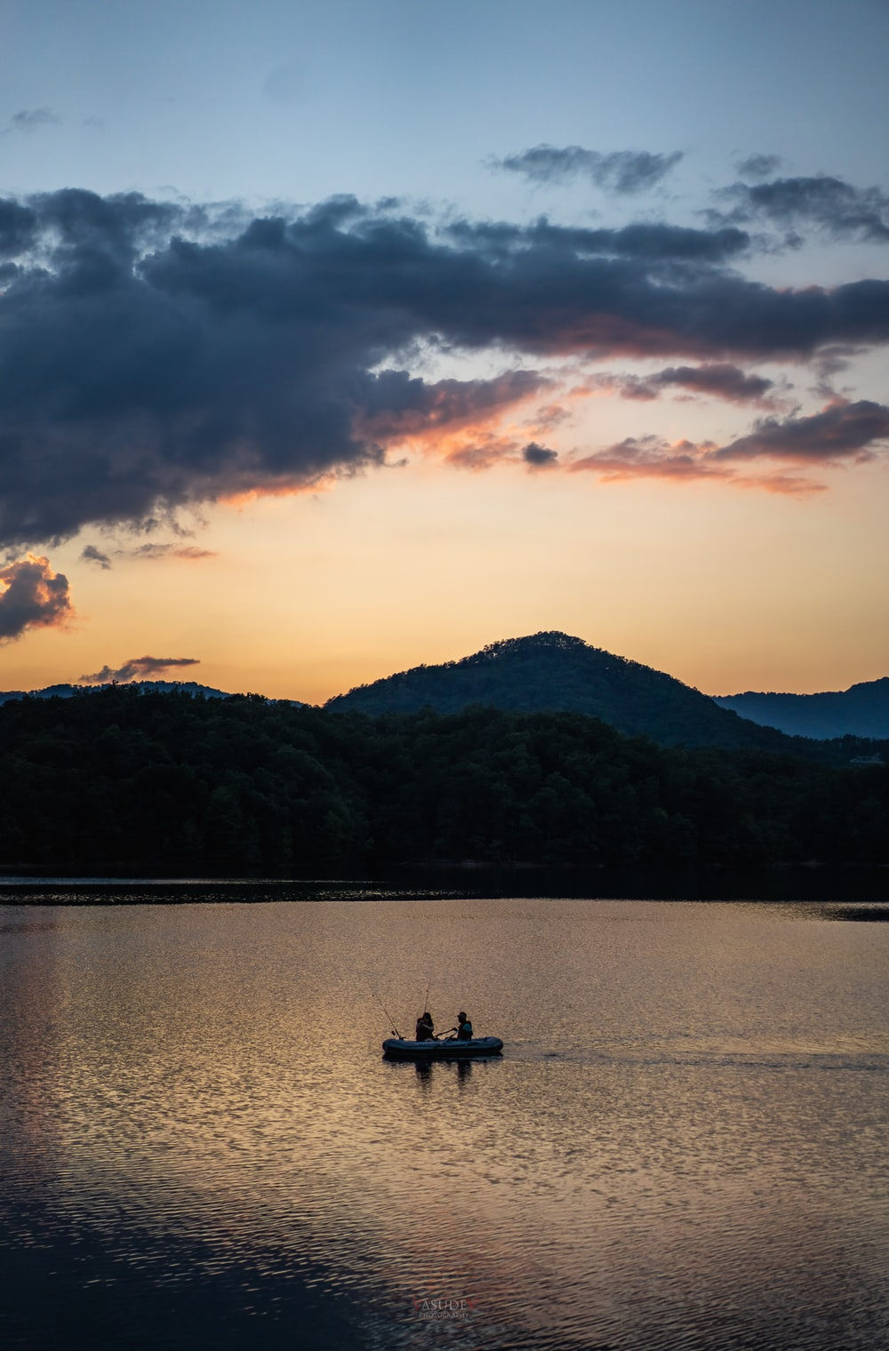 silhouette of people riding boat on lake during sunset