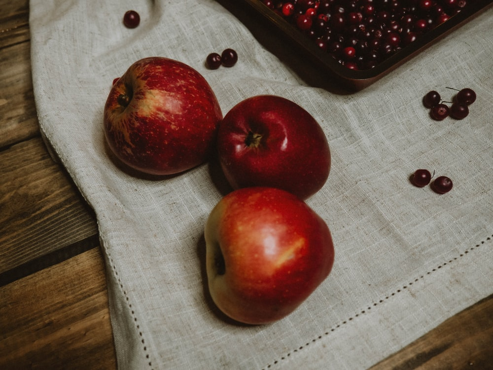 red apples on white textile