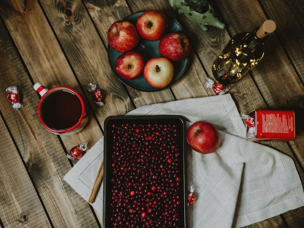 red apple fruit on black tray beside red ceramic mug