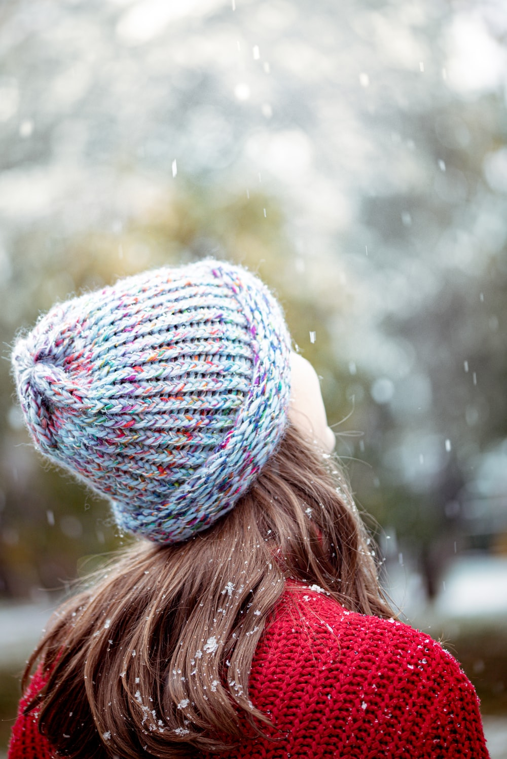 woman in blue knit cap and red jacket