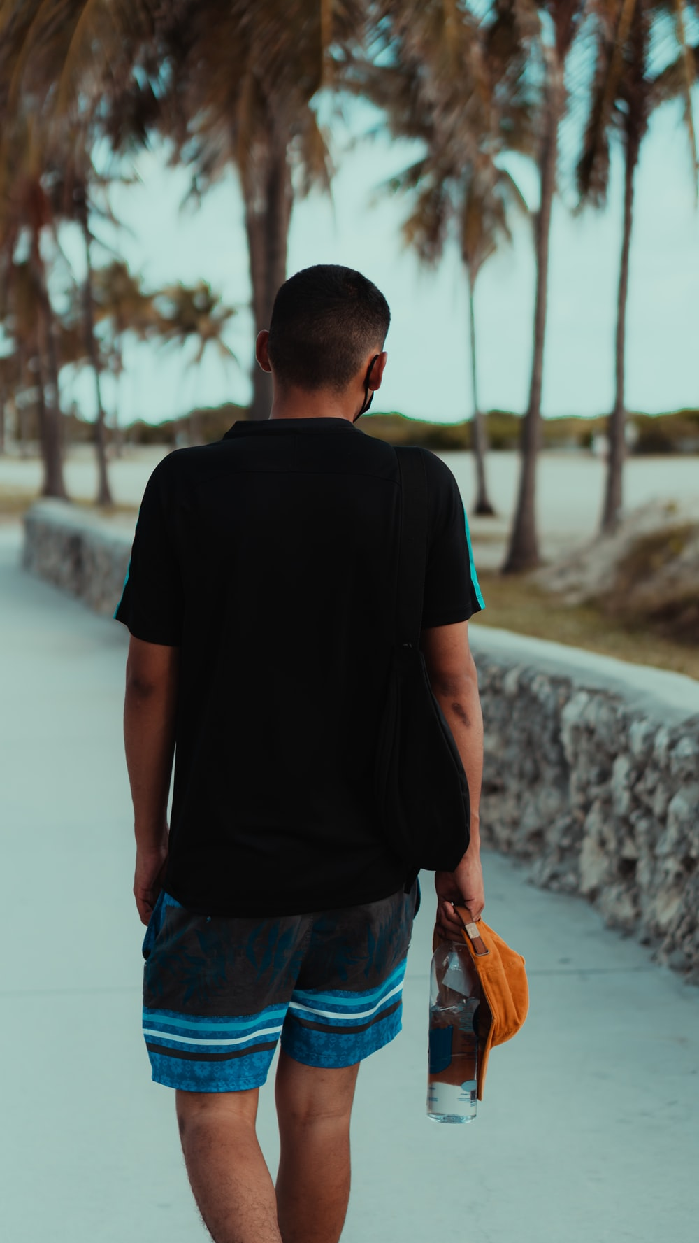 man in black crew neck t-shirt and blue denim shorts standing on gray concrete pavement