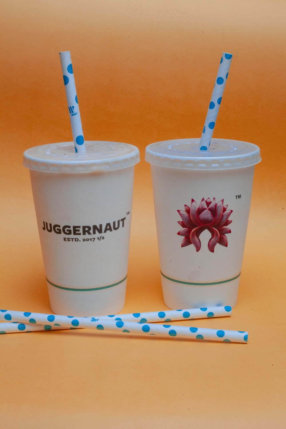 two white plastic cups with straws