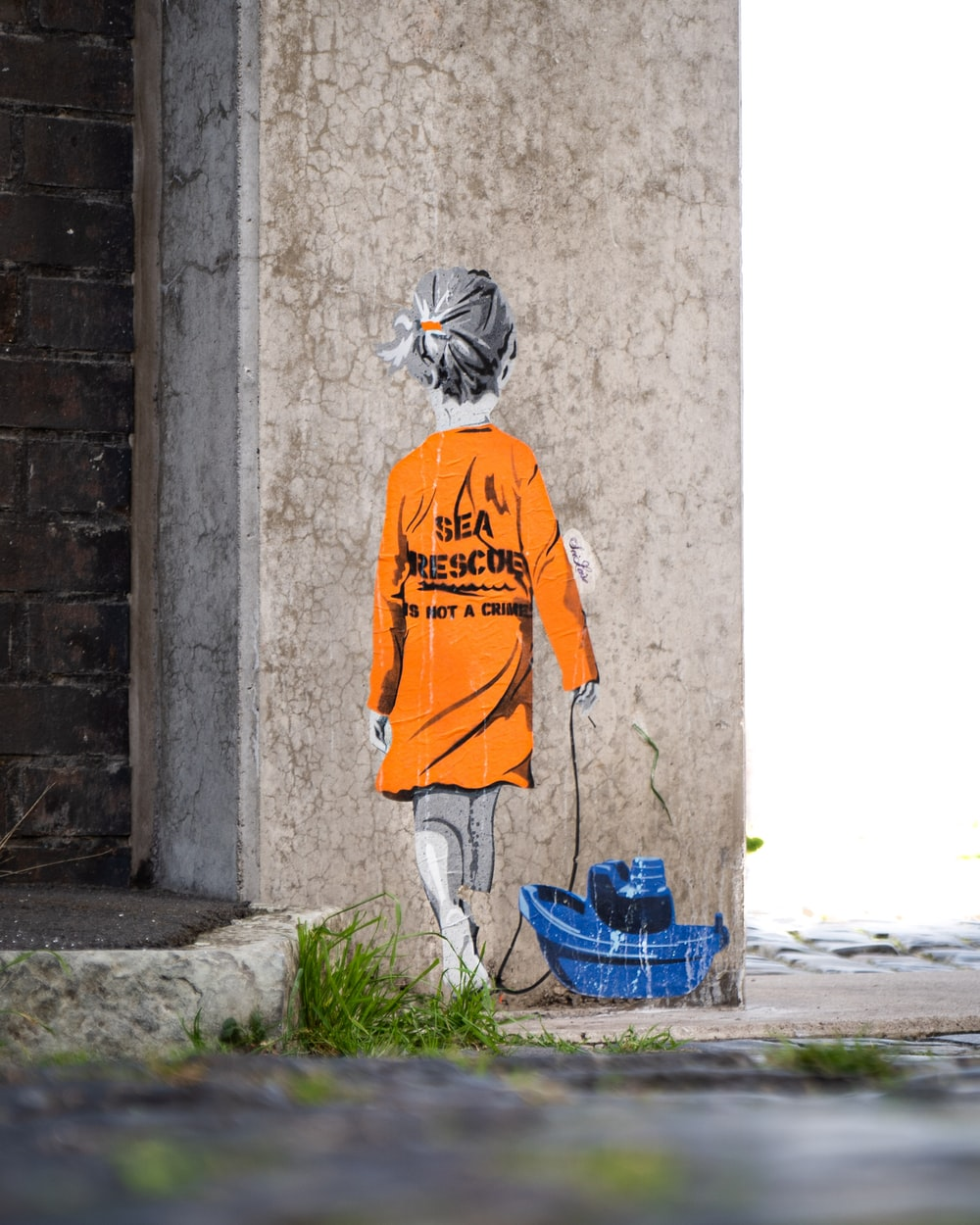 person in orange shirt wearing white and black mask standing beside gray concrete wall during daytime