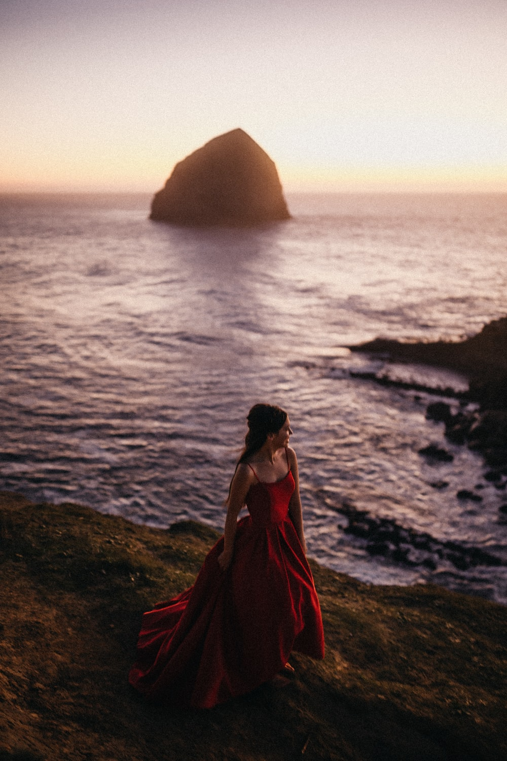 woman in red dress standing on rock near body of water during daytime