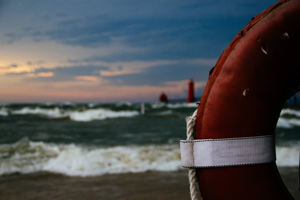 red and white inflatable ring on beach shore during daytime