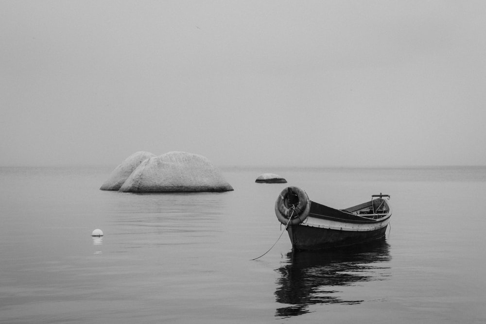 grayscale photo of canoe on water