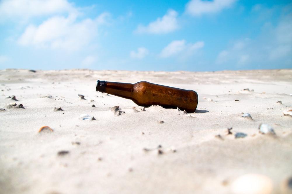 brown glass bottle on white sand during daytime