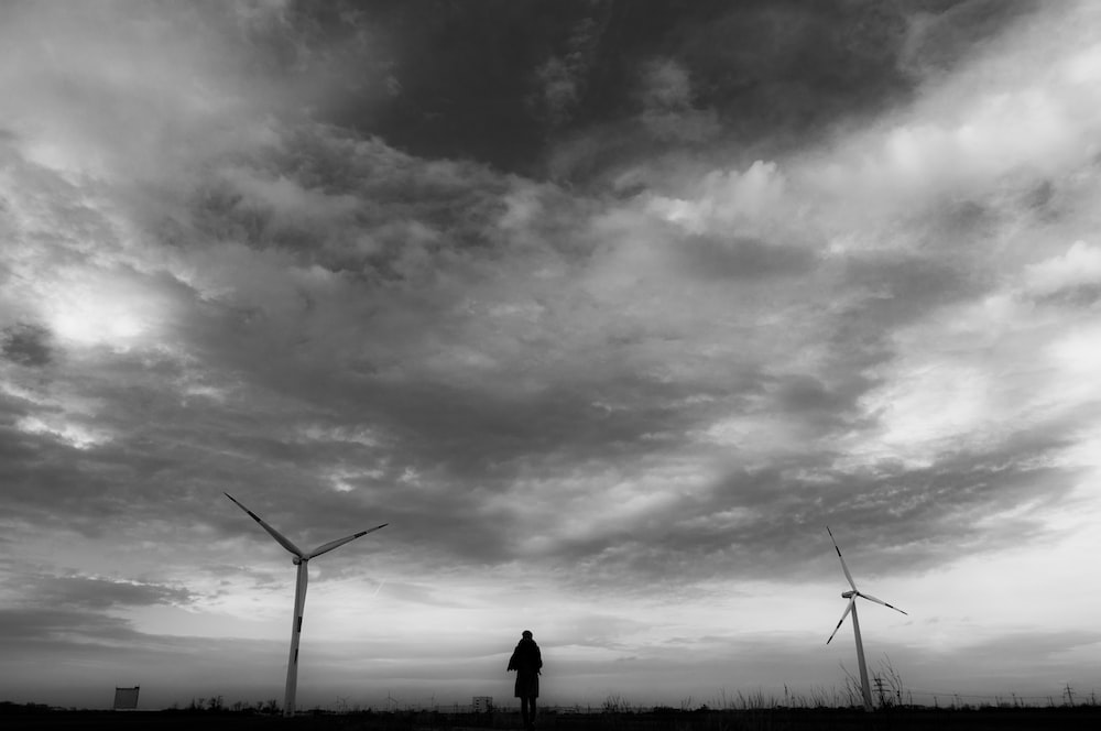silhouette of person standing near wind turbines under cloudy sky during daytime