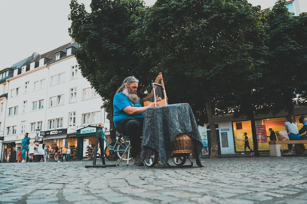 man and woman sitting on chair near green trees during daytime