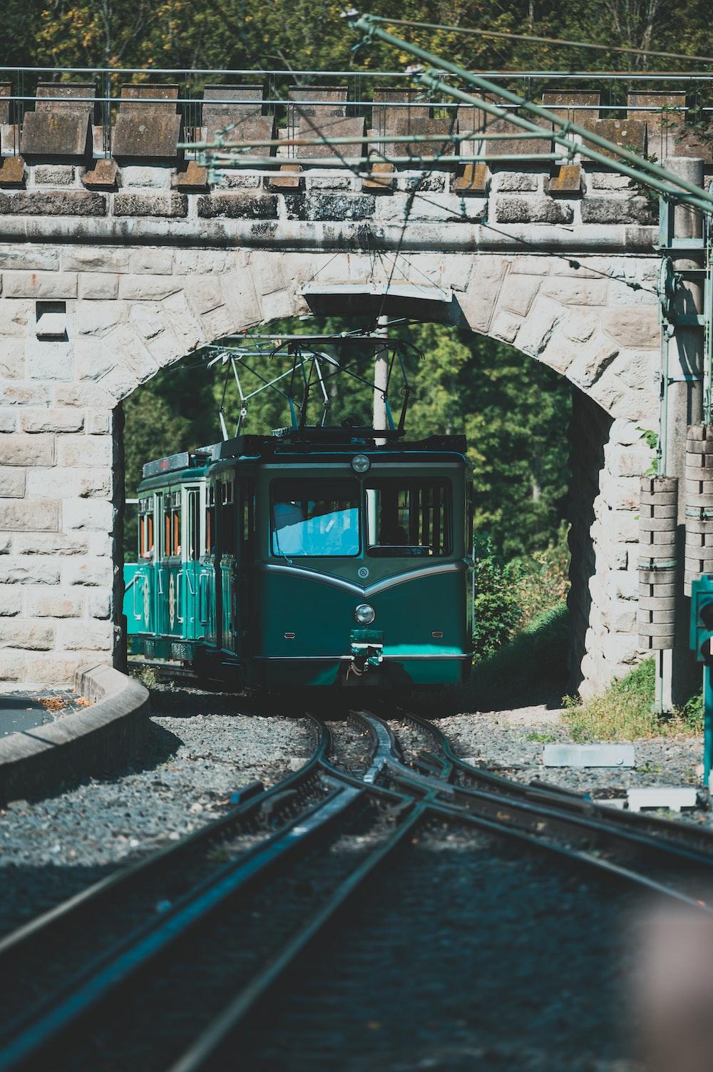 green train on rail tracks
