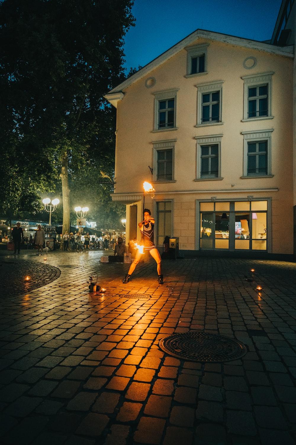 woman in black dress walking on sidewalk during night time