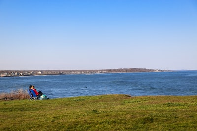 people sitting on green grass field near body of water during daytime cape cod teams background