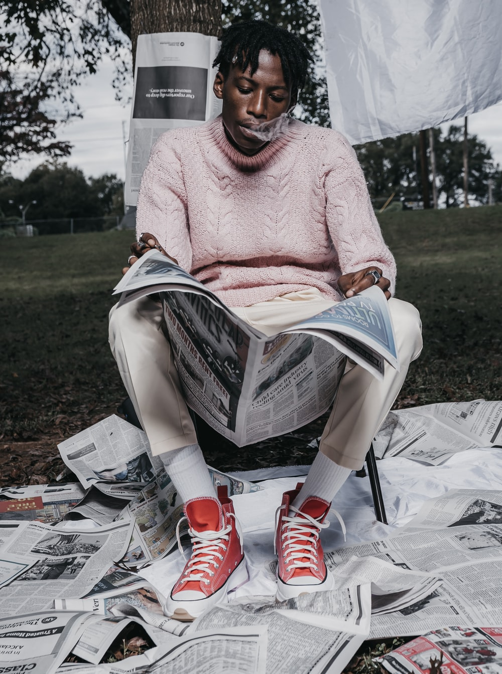 woman in pink knit sweater and white pants sitting on white plastic chair